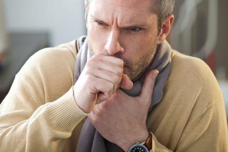 Man coughing clutching throat